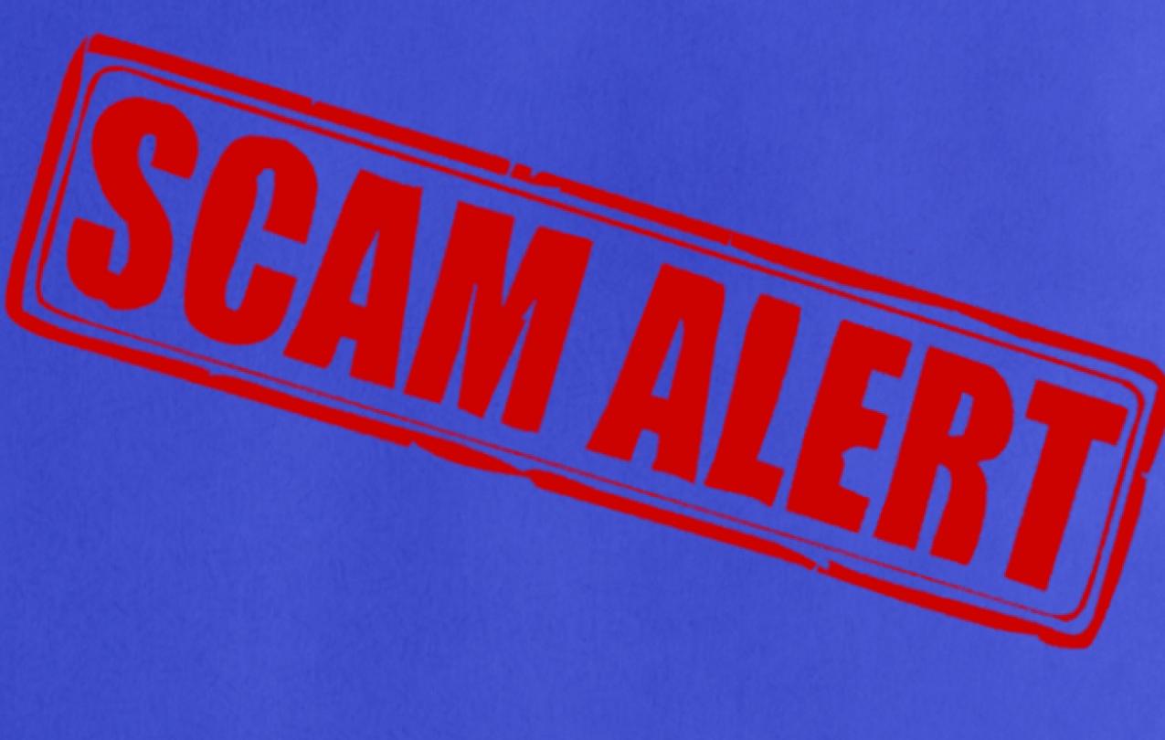 "Red ""SCAM ALERT"" stamp on a blue background"