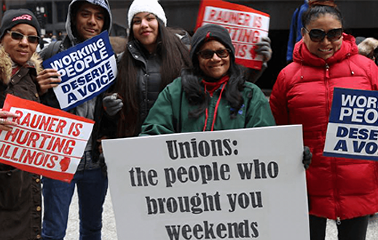 """AFSCME members in Illinois rally with signs that say """"Working people deserve a voice"""" and """"Rauner is hurting Illinois."""""""